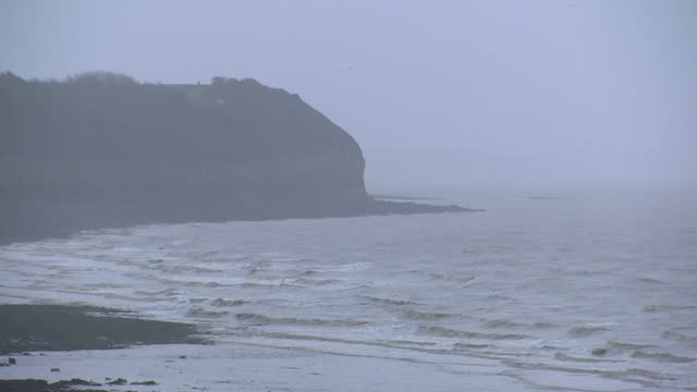 Shows exterior shots stormy waves approaching shore with headland at edge of bay seen in distance with murky air as Storm Eleanor approaches West...