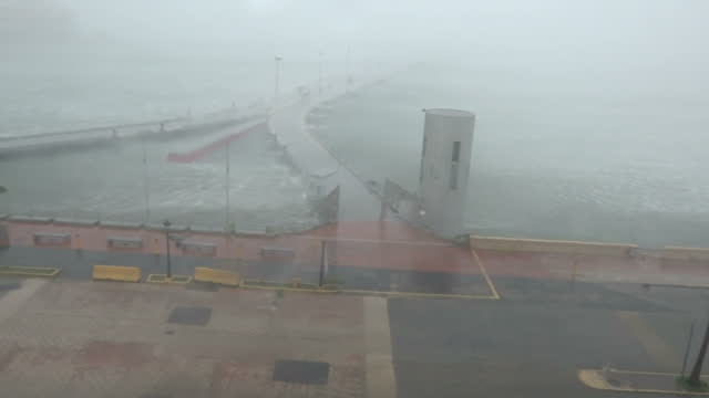 shows exterior shots strong wind driving rain before it along sea front as hurricane maria arrives in puerto rico with sound of hurricane hitting... - 2017 stock-videos und b-roll-filmmaterial