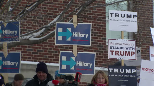 Shows Exterior shots supporters of various presidential candidates outside polling station in New Hampshire with posters and placards in support of...