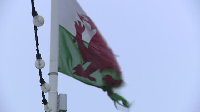 Shows exterior shots tattered Welsh flag with red dragon on it blowing around in blustery wind and string of light bulbs across shot as Storm Eleanor...