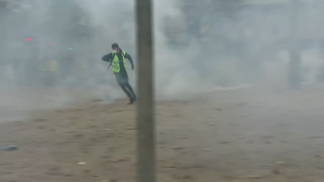 Shows exterior shots tear gas being fired at the protesters wearing yellow vests near the Arc de Triomphe with one protester throwing a cannister...