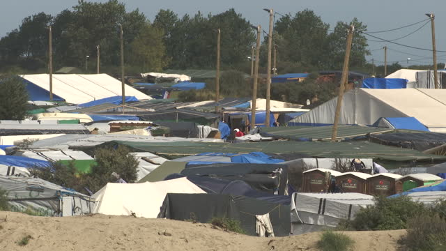 shows exterior shots tents and make shift shelters that make up the jungle camp in calais hundreds of refugee children are still living in the... - calais stock videos and b-roll footage