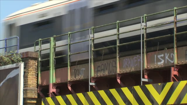 shows exterior shots thameslink train crossing railway bridge covered in graffiti near loughborough junction station. british transport police... - railway junction stock videos & royalty-free footage