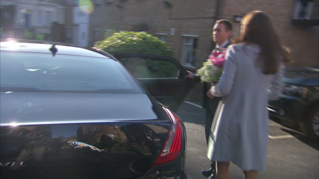 Shows exterior shots the Duchess of Cambridge walking with flowers saying goodbye to some of the guests before getting into car being driven off on...