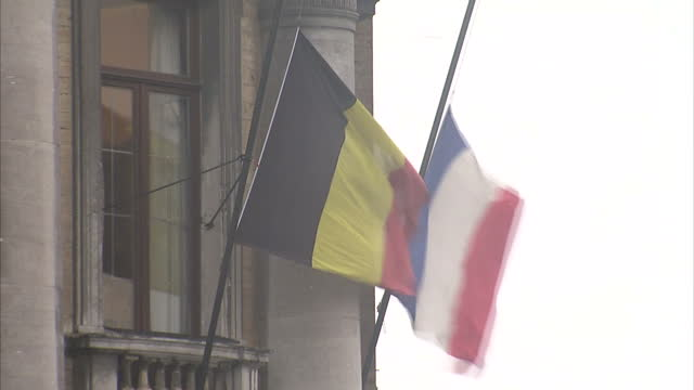 Shows Exterior shots town square in Molenbeek a suburb of Brussels with people walking about in the rain and close ups Belgian and French flags at...