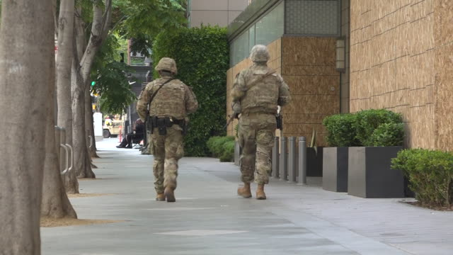shows exterior shots two anonymous armed national guard soldiers walking along pavement past pboarded up shop windows in los angeles california is... - weaponry stock videos & royalty-free footage
