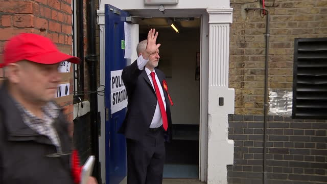 Shows exterior shots UK Labour Party Leader arriving at Polling Station and posing for photographers smiling and giving thumbs up gesture on voting...