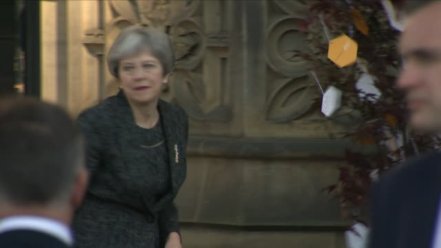 shows exterior shots uk prime minister theresa may walking out of manchester cathedral tying a message to the tree and departing a memorial service... - prime minister of the united kingdom stock videos and b-roll footage