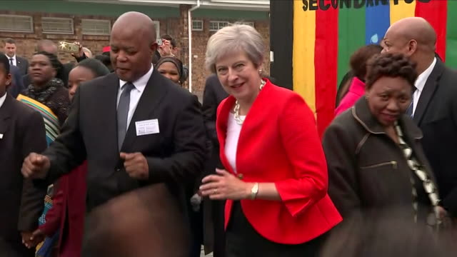 shows exterior shots uk prime minister theresa may watching pupils dance on visit tothe id mkhize secondary school in gugulethu about 15km from the... - theresa may stock videos & royalty-free footage