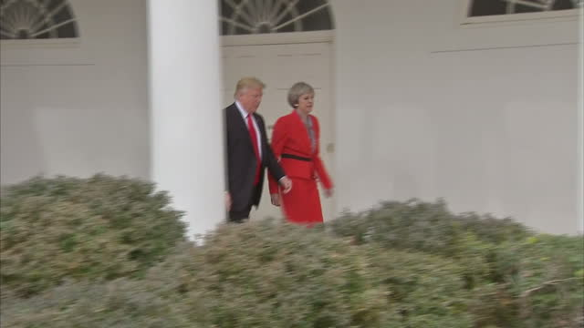Shows exterior shots US President Donald Trump holding hands with UK Prime Minister Theresa May as they walk along colonnade at The White House on...