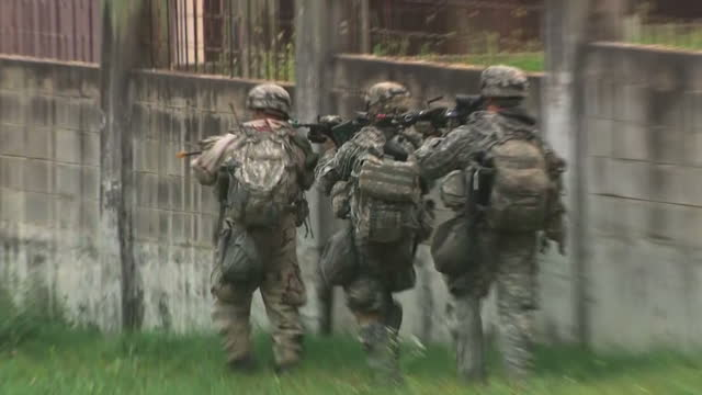 shows exterior shots us soldiers running between buildings and along perimeter wall in an urban environment during training exercise it's leader has... - esercitazione militare video stock e b–roll
