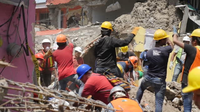 vídeos de stock, filmes e b-roll de shows exterior shots volunteers digging through rubble of collapsed building and removing buckets and debris from site along a human chain in... - 2017