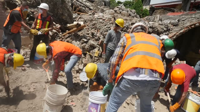 Shows exterior shots volunteers digging through rubble of collapsed building and removing buckets and debris from site in aftermath of earthquake on...