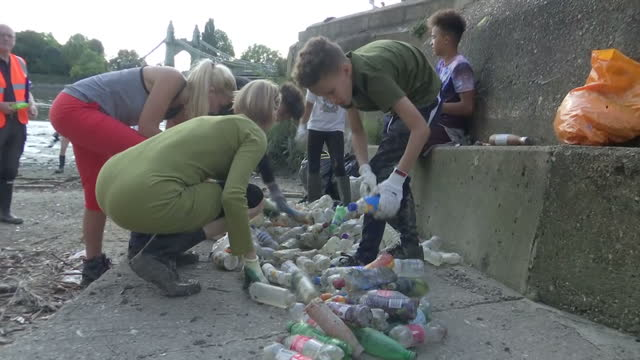 shows exterior shots volunteers picking up litter and plastic bottles underneath hammersmith bridge in london and close ups of litter along the banks... - fluss themse stock-videos und b-roll-filmmaterial