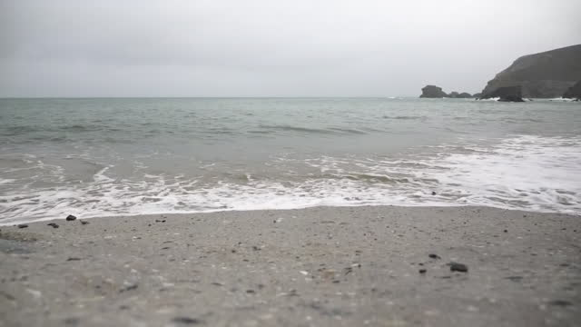 vídeos de stock, filmes e b-roll de shows exterior shots waves breaking on pebbles on beach on grey miserable winter's day, on 23rd november, 2020 in cornwall, england, united kingdom - pedra solta