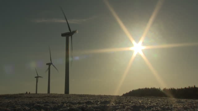vidéos et rushes de shows exterior shots wind turbines turning in field at wind farm with sun shining low in winter sky on 28th december, 2017 in scotland, uk - écosse