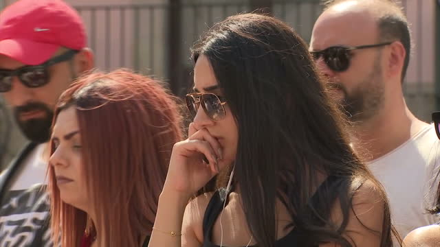 shows exterior shots woman wearing sunglasses looking upset as she looks at flowers and tributes left for victims of terror attack on la rambla... - temporäre gedenkstätte stock-videos und b-roll-filmmaterial
