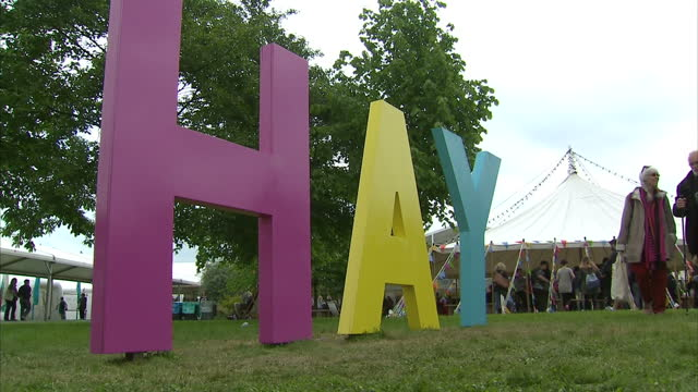 Shows exterior shots word sculpture spelling 'HAY' with festival goers walking around and sitting on deck chairs on May 30 2016 in HayonWye Wales