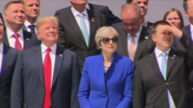 Shows exterior shots world leaders watching a flyby of NATO aircraft at the opening ceremony for the 2018 NATO Summit at the NATO Headquarters Donald...