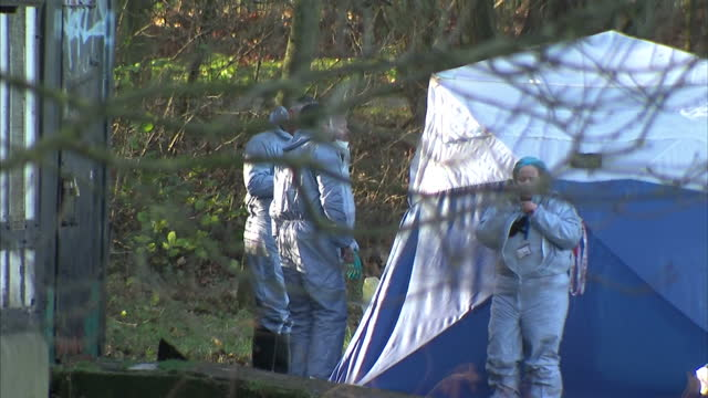 Shows exterior shtos forensics officers and forensics tent set up insied police cordon area over site where body of woman found in Finsbury Park A...
