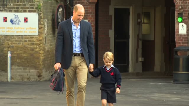 shows exterior shtos prince william duke of cambridge holding prince george's hand as he arrives for his first day at school with his teacher walking... - 1日目点の映像素材/bロール