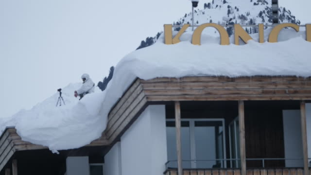 Shows exterior shtos sign for DAVOS on hotel roof half covered in snow Exterior shots armed guards on top of hotel at World Economic Forum World...