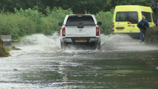 shows exterior shtos vehicles driving through flood water across road in Grinton Yorkshire Dales For parts of the UK last week's heatwave is a...