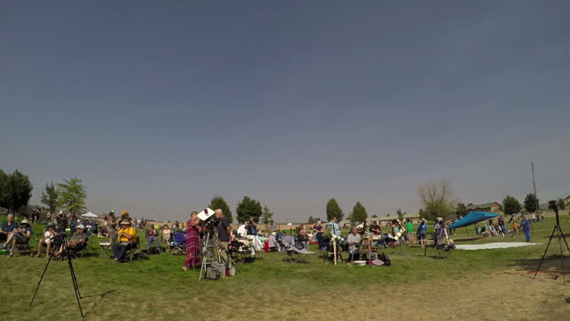 Shows exterior timelapse shots crowds watching the total solar eclipse as sky darkens and lightens again after moon passes between Earth and the Sun...