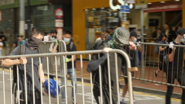 shows exterior wide shots protesters picking up crowd control barriers and starting to construct barricades across roads in causeway bay in hong... - hong kong island stock videos & royalty-free footage
