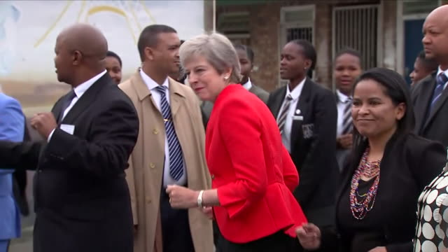 shows exteriorshots uk prime minister theresa may dancing on visit to the id mkhize secondary school in gugulethu about 15km from the centre of cape... - theresa may stock videos & royalty-free footage