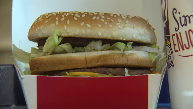 shows interior close up shots mcdonald's big mac burger in takeaway container interior shots big mac burger being assembled by fast food restaurant... - mcdonald's stock videos & royalty-free footage