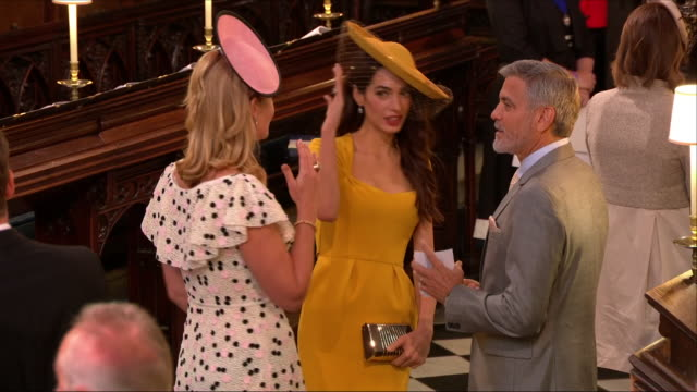 shows interior shots actor george clooney and his wife amal clooney chatting to tv presenter dan snow and his wife lady edwina louise grosvenor in st... - ジョージ・クルーニー点の映像素材/bロール