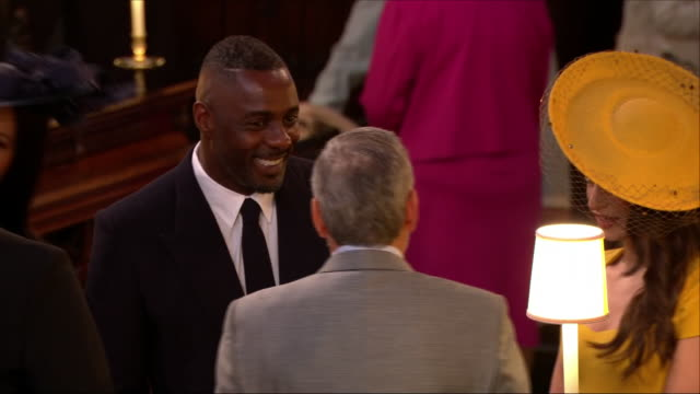 Shows interior shots actor George Clooney and his wife Amal Clooney chatting to actor Idris Elba in St George's Chapel at the wedding of Prince Harry...