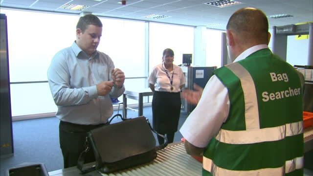 shows interior shots airport security training with passengers placing bags on airport security xray machine and security staff performing searches... - säkerhetsskanner bildbanksvideor och videomaterial från bakom kulisserna
