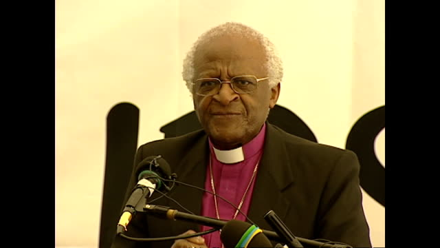 Shows interior shots Archbishop Desmond Tutu giving speech soundbite making joke about taking credit for round of applause for god on April 10 2004...