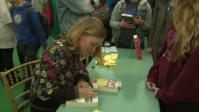 vídeos de stock e filmes b-roll de shows interior shots author holly smale signing books for people at author book signing event at hayonwye festival on may 30 2016 in hayonwye wales - hay on wye