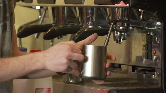 shows interior shots barista in coffee shop warming or frothing milk in metal jug on 13th february, 2017 in alexandria, virginia, united states - jug stock videos & royalty-free footage
