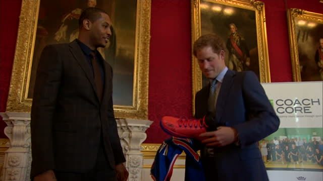 Shows interior shots Carmelo Anthony presenting Prince Harry with New York Nicks basketball trainers shirt with the name Wales printed on the back at...