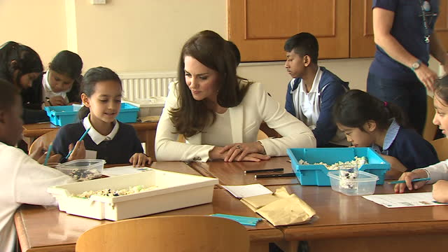 shows interior shots catherine , duchess of cambridge, helping children with a task in a workshop at an 1851 charity event in london docklands.... - 作業場点の映像素材/bロール