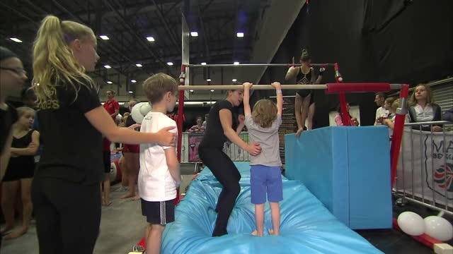 shows interior shots children having a go at turning round bar at gymnastics session at free 'i am team gb' event in coventry olympians returning in... - gymnastics bar stock videos & royalty-free footage