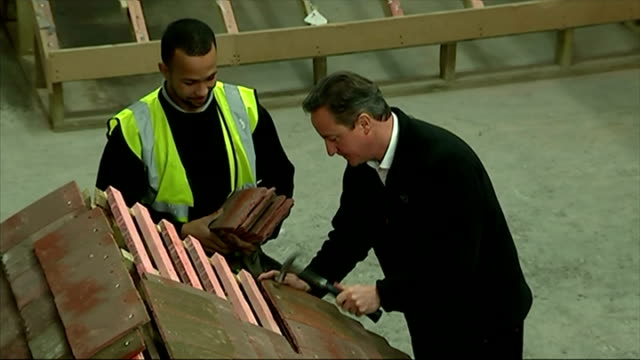 shows interior shots david cameron fixing tiles to a mock roof in warehouse with hammer as former apprentice lynden blackwood hands him tiles on... - früherer stock-videos und b-roll-filmmaterial
