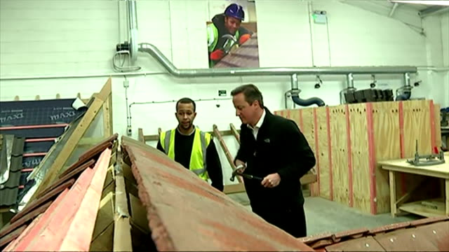 shows interior shots david cameron working with former apprentice lynden blackwood on mock roof in warehouse on january 12 2015 in nottingham england - früherer stock-videos und b-roll-filmmaterial