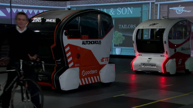 shows interior shots driverless aurrigo pods in test environment moving around mocked up streets being tested for safety including stopping for... - fleet of vehicles stock videos and b-roll footage