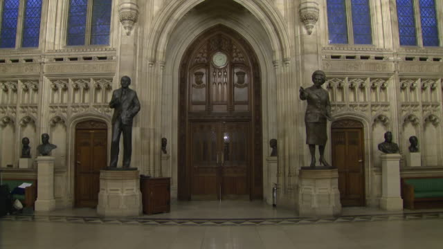 shows interior shots entrance doors to the house of commons debating chamber statues and busts of various politicians including margaret thatcher in... - 庶民院点の映像素材/bロール