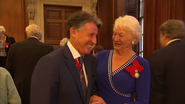 shows interior shots former athletes lord sebastian coe and dame mary peters talking and laughing at reception. the queen and prince philip attended... - メアリー ピータース点の映像素材/bロール