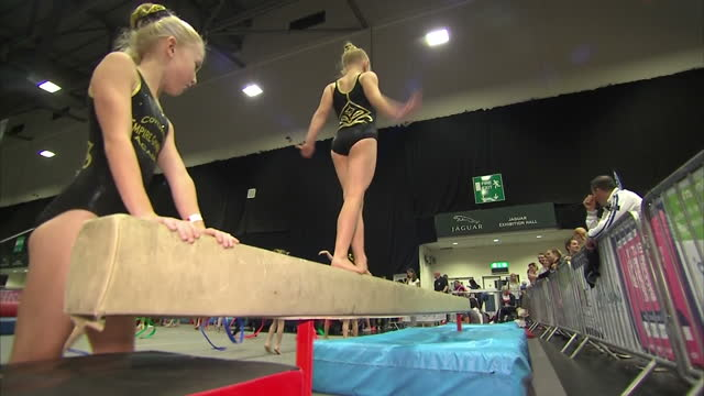 shows interior shots girls of varying abilities practising jumping and bar at gymnastics session at at free 'i am team gb' event in coventry... - gymnastics bar stock videos & royalty-free footage