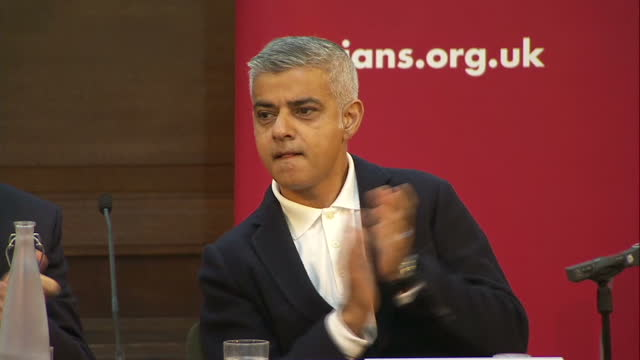 Shows interior shots hecklers and protesters being escorted from hall by police as London Mayor Sadiq Khan joins the audience applause from stage...