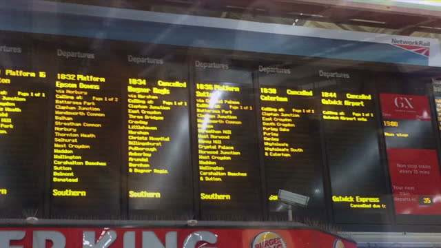 Shows interior shots huge crowds of commuters in Victoria Station departure boards showing cancelled trains the day before the strike and signs and...