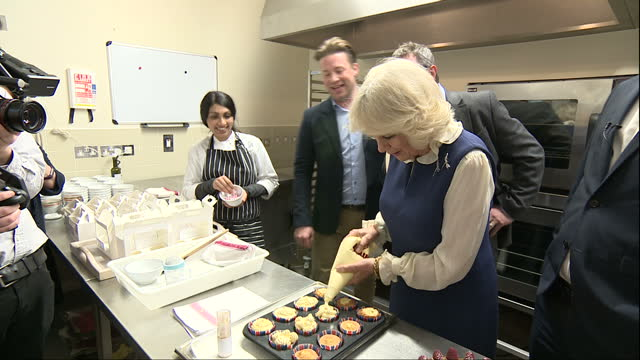 shows interior shots jamie oliver showing camilla, duchess of cornwall, how to hold an icing piping bag before she has a go at icing several... - jamie oliver stock videos & royalty-free footage