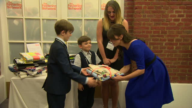 Shows Interior shots Kate Catherine Duchess of Cambridge meeting foster children Rowan and Ambrose and being presented with a gift of handmade...